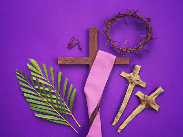 A Christian crosses, three rusty nails, a woven crown of thorns and palm leaves on purple background. (Getty Images/iStockphoto)