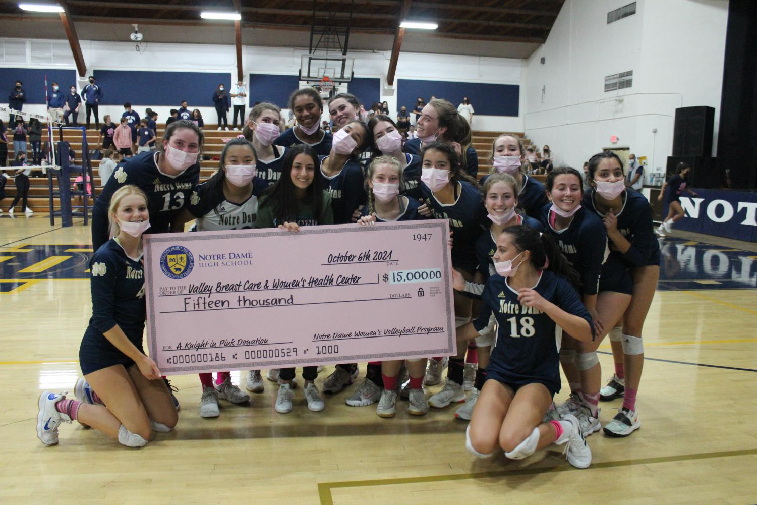 The team presents the check to a representative from the Valley Breast Care and Women's Health Center. The volleyball program  raised $15,000, three times the amount of their original goal.